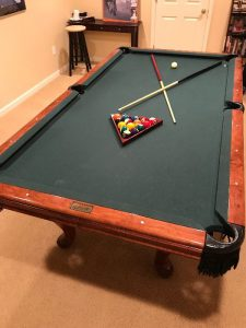Pool table with balls and sticks assorted on top